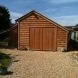 Single bay garage with Sapelle doors and log store